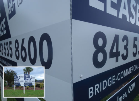Blue and white alumalite realty sign with text that reads: BRIDGE COMMERCIAL