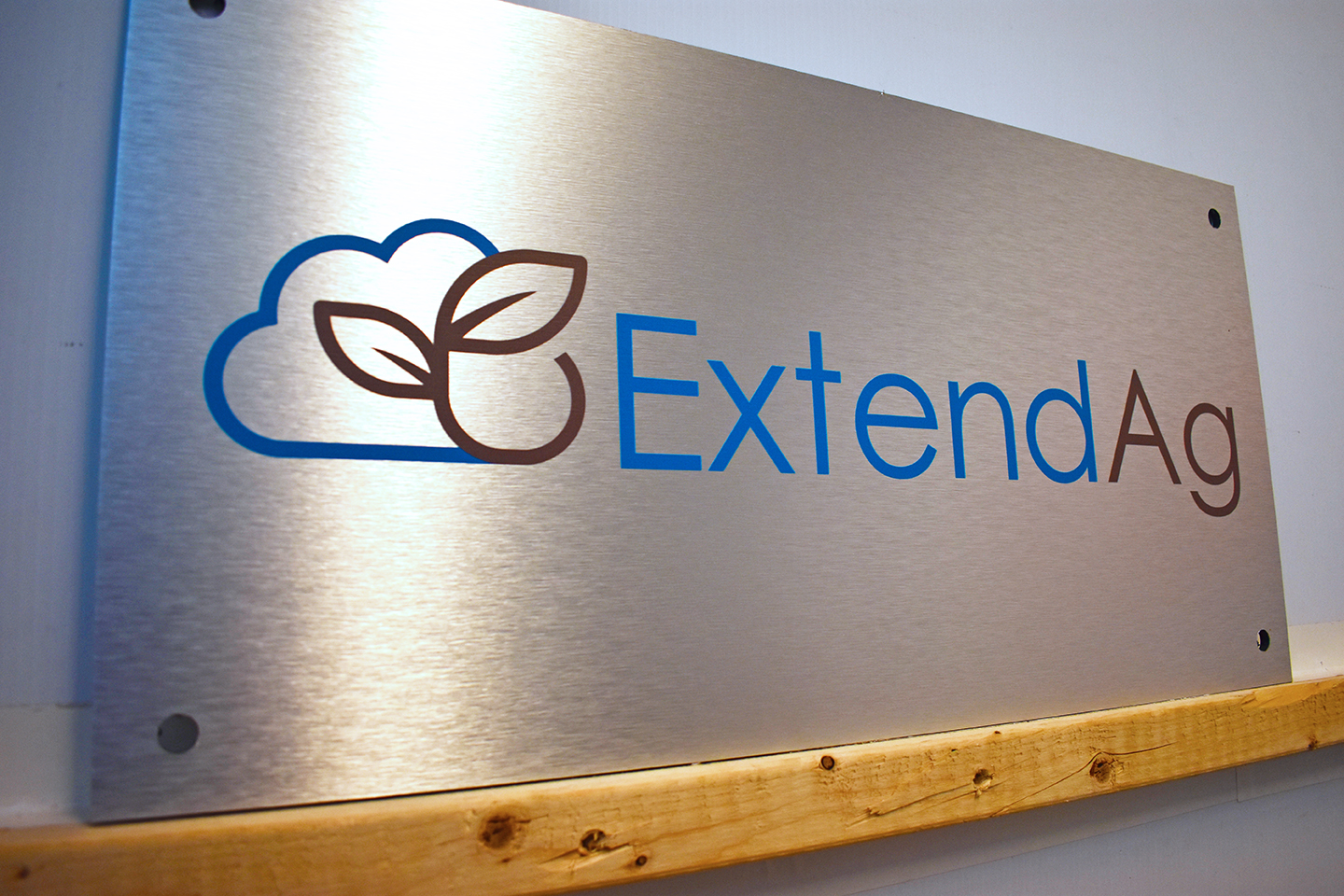 Brushed silver dibond sign with graphic of cloud and plant and text that reads: ExtendAg