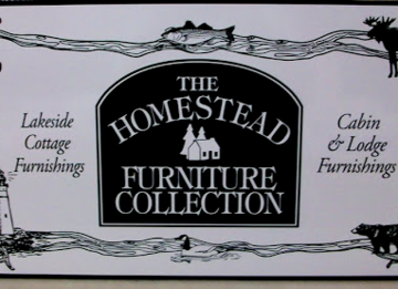 Black and White Alumalite wall sign that reads: THE HOMESTEAD FURNITURE COLLECTION