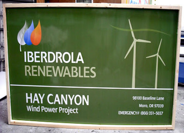Painted green alumalite sign with text that reads: IBERDROLA RENEWABLES HAY CANYON Wind Power Project