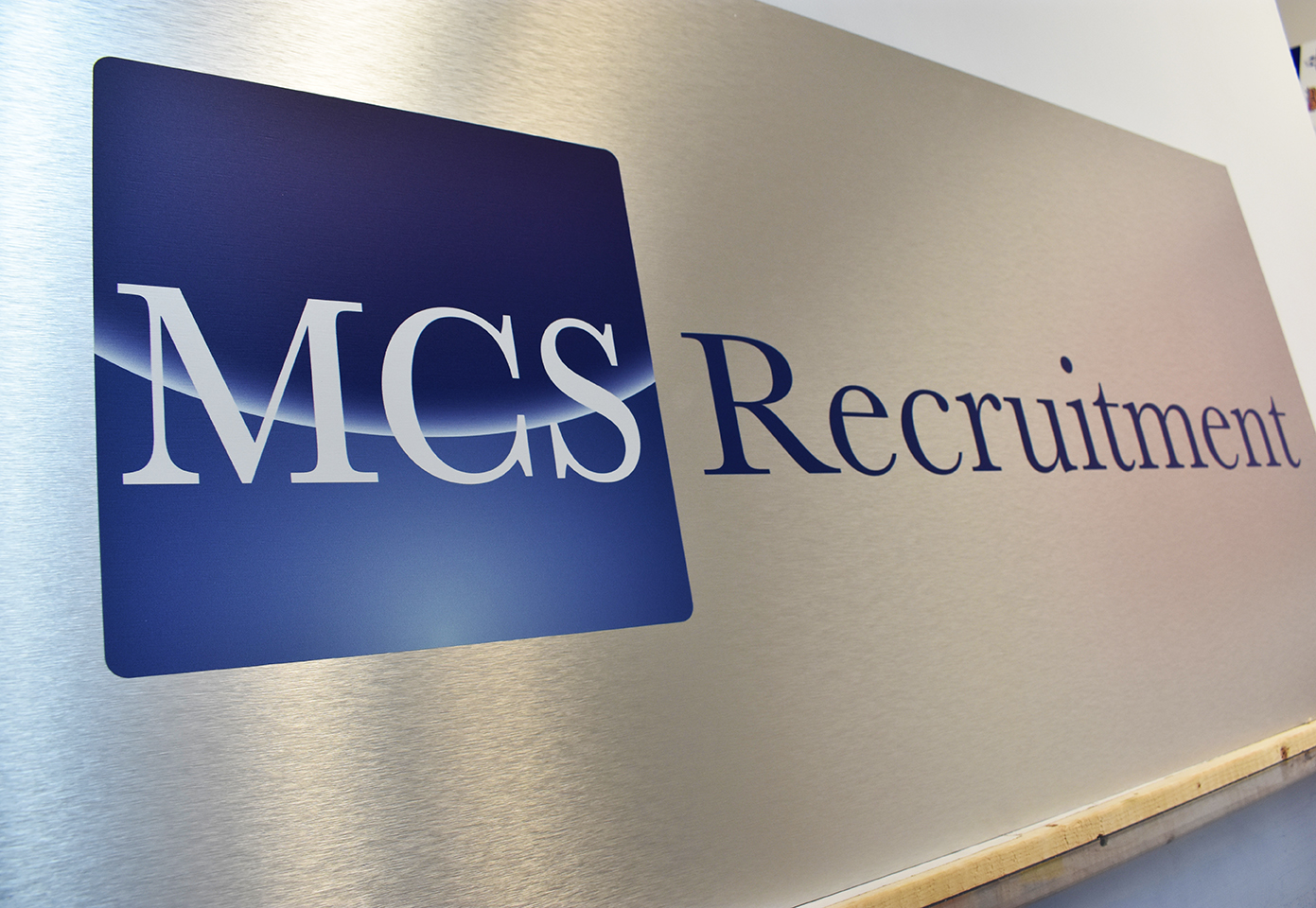 Brushed silver dibond sign with blue and white text that reads: MCS Recruitment