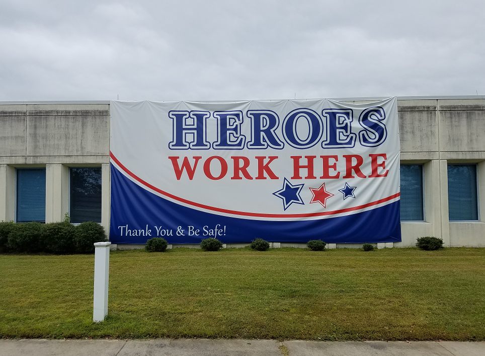 Red, white, and blue banner on building with text that reads: Heroes