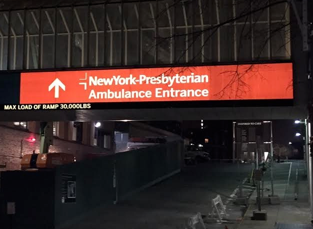 Reflective red and white sign on hospital wall with text that reads: New York-Presbyterian Ambulance Entrance