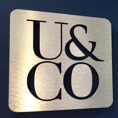 Brushed aluminum sign with four black letters. Text reads: U&CO