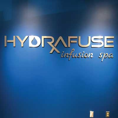 Blue sign with brushed gold alumnium letters. Text reads: Hydrafuse infusion spa