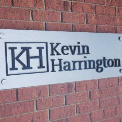 Brushed silver sign backing with black 3d letters and logo. Text reads: KH. Kevin Harrington