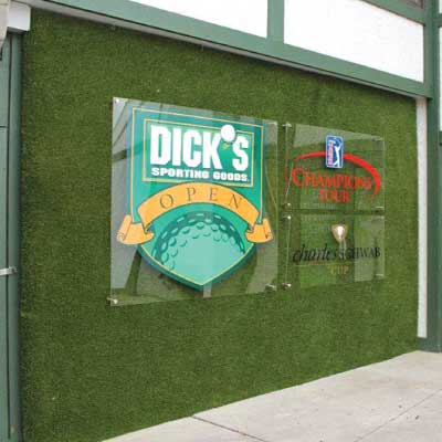 Group of three clear acrylic signs each with a different golf related logo on top of a faux grass wall background. Text reads: Dick's Sporting Goods, OPEN. Champion's Tour. Charles Schwab Cup.
