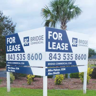 Large real estate land for lease white and blue sign in a front yard with flowers and palm tree in background. Text: For lease, Bridge Commerical
