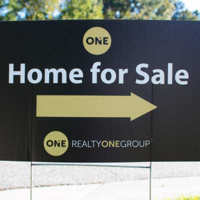 Black with white letters sign and gold arrow with logo. Text reads: One. Home for Sale