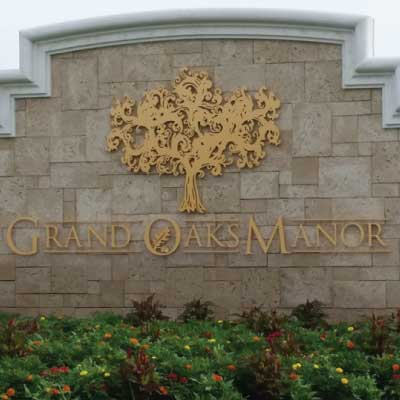 Gold text and logo custom 3d logo on tiled monument neighborhood entrance. Text reads: Grand Oaks Manor