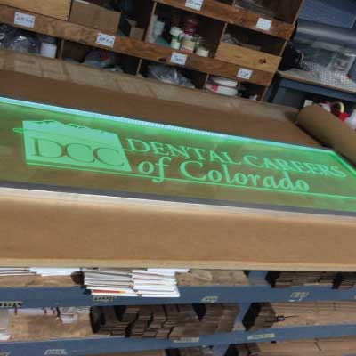 Acrylic with glowing green text and logo edge lighted indoor sign. Text reads: DCC. Dental Careers of Colorado