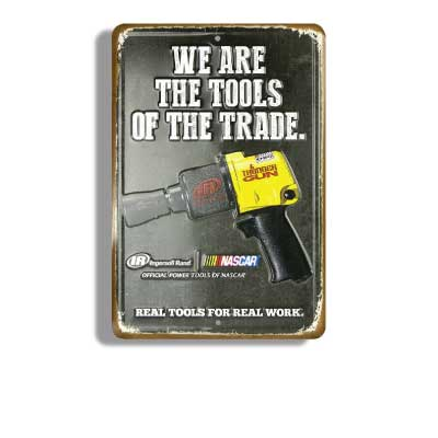 Black with rusty edges stamped metal embossed sign with picture of Nascar air ratchet gun. Text reads: We are the tools of the trade. Ingress Rand. Real tools for real work.
