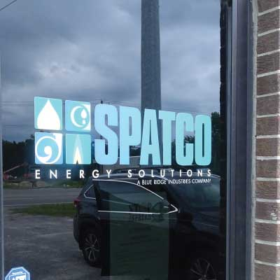 Blue letters and logo on glass door storefront. Text reads: SPATCO. Energy Solutions.