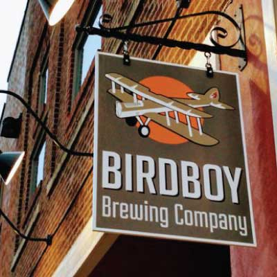 Brown hanging sign with white text and early flight era prop plane logo. Text reads: Birdboy Brewing Company