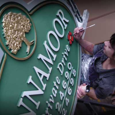 Inset green high density hdu sign with white lettering and gold logo hand painted by lady. Text reads: ...NAMOOR Private Drive