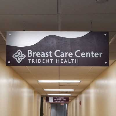 Hanging indoor metal sign with dark wood wavy mid-section. Text reads: Breast Care Center, Trident Health