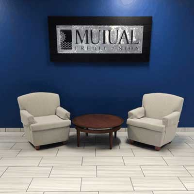 Indoor metal lobby sign with blue text on a blue wall above two white chairs. Text reads: Mutual Credit Union