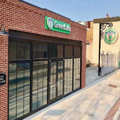 Green sign with white 3D text and caduceus logo over one-story brick business building. Text reads: GreenLabs