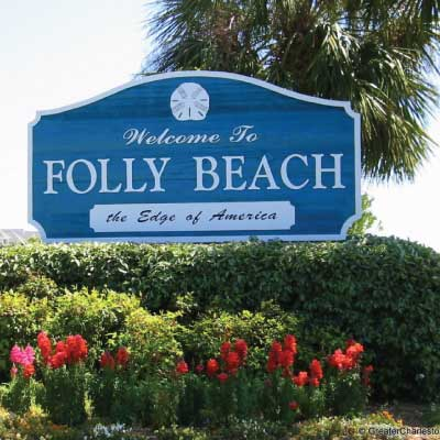 Blue textured redwood sandblasted sign with painted white letters. Text reads: Welcome To Folly Beach. The Edge of America.