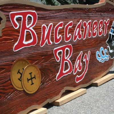 Faux wood textured and stained solid wood sign with red and white outlined text with black pirate ship graphic. Text reads: Buccaneer Bay