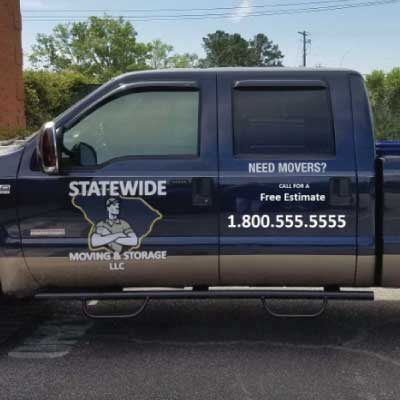 White logo and lettering on side of truck. Logo is a strong man on top of the outline of South Carolina. Text reads: STATEWIDE Moving and Storage LLC. Need Movers? Call for a free estimate