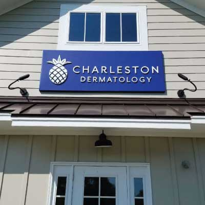 Blue sign with white 3D text and pinapple logo over tan vinyl business store. Text reads: Charleston Dermatology