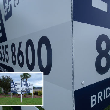 Blue and white alumalite real estate sign with text that reads Bridge-Commercial
