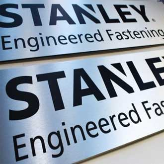 Two brushed silver dibond engineering firm signs on a table