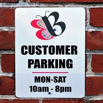 Customer parking sign with butterfly company logo and hours reading Monday through Saturday 10am to 8pm
