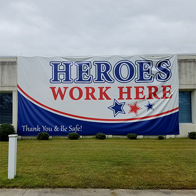 Vinyl banner on side of building reading Heroes Work Here