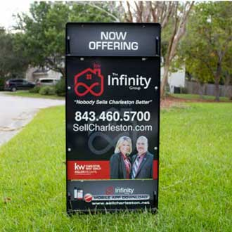The Infinity Group's black and red real estate brokerage sign on a lawn