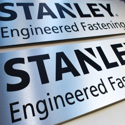 Brushed silver sign with black letters. Text reads: STANLEY. Engineered Fastening.