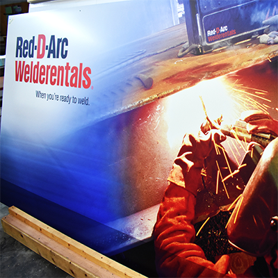 Painted aluminum business sign with picture of welder and text that reads Red D Arc Welderentals