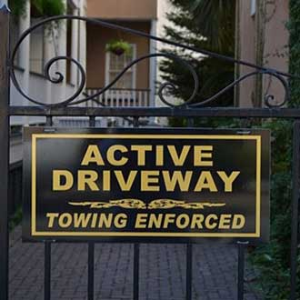 Sign on wrought iron fence reading active driveway towing enforced
