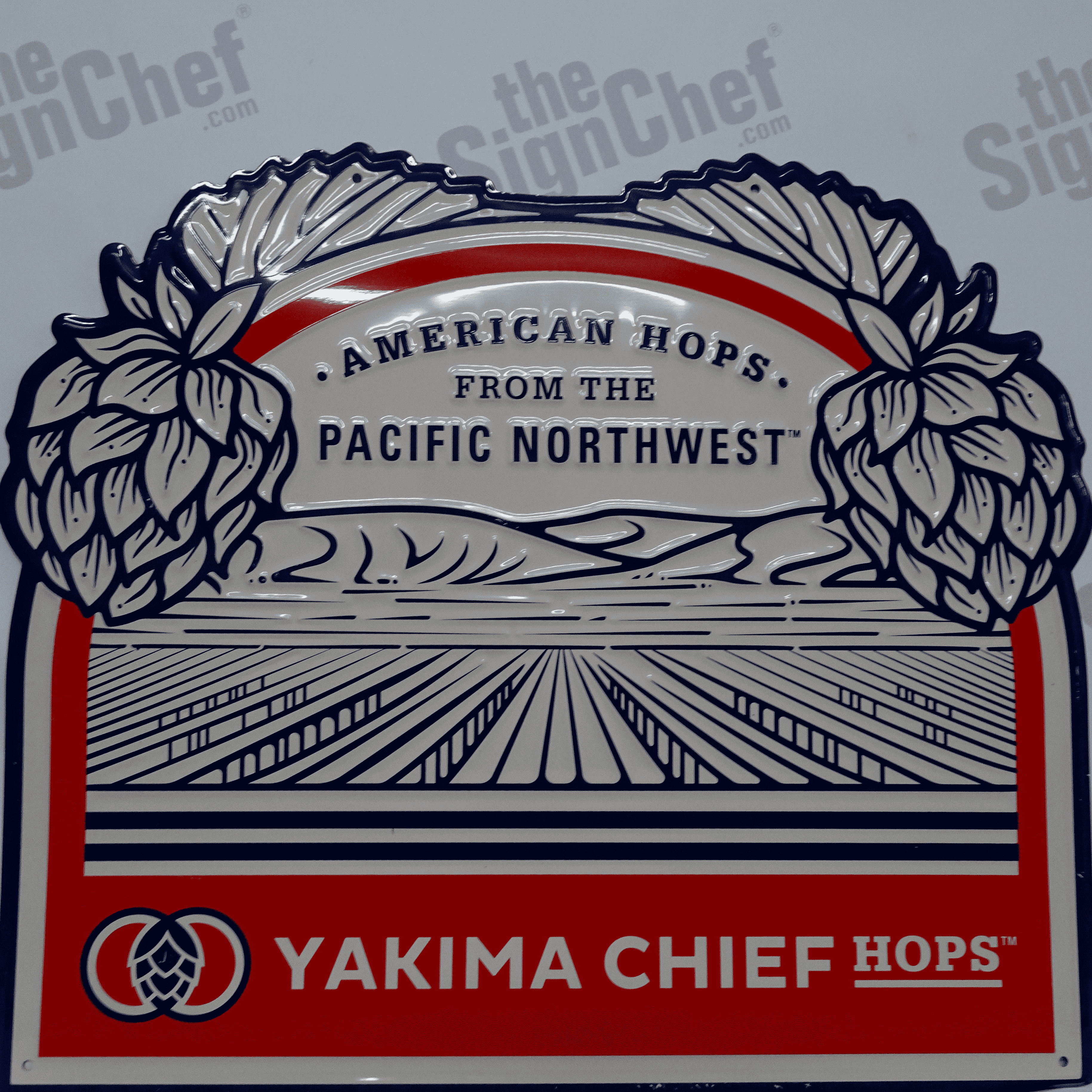 Orange, red, and white vintage sign with text that reads: Yakima Chief Hops