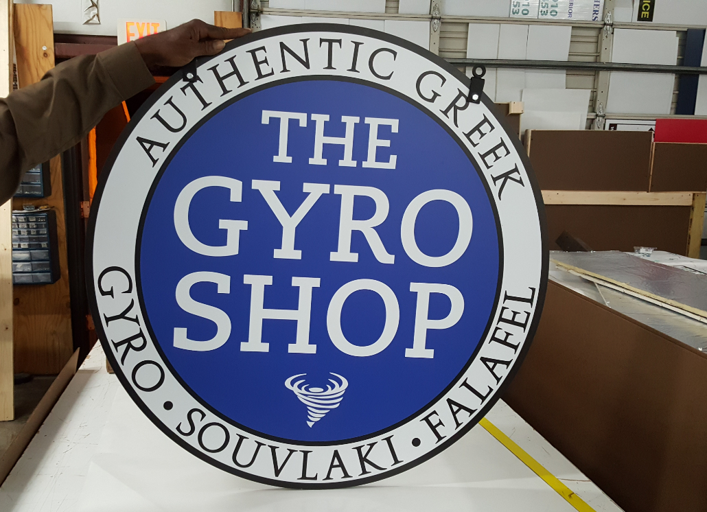 Painted, circular aluminum hanging sign with text that reads AUTHENTIC GREEK THE GYRO SHOP GYRO SOUVLAKI FALAFEL