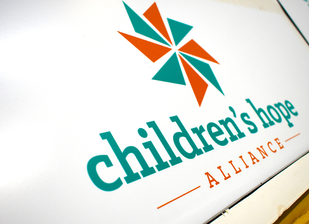 Turqoise, orange, and white ARMOUR-wood wall sign with windmill graphic and text that reads: children's hope ALLIANCE