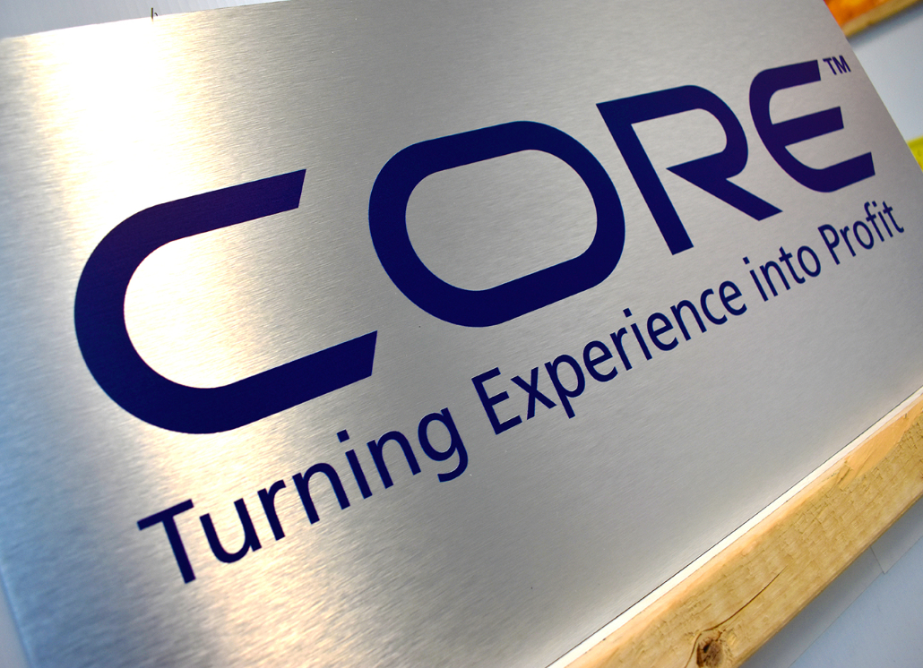 Brushed silver aluminum sign with text that reads: CORE Turning Experience into Profit