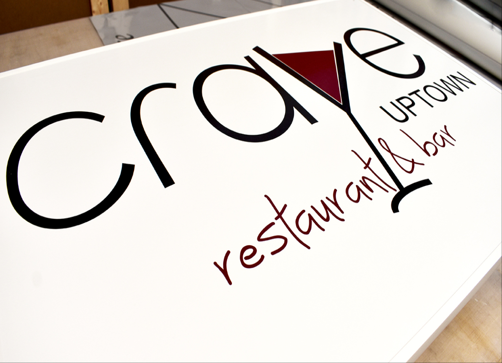 White alumalite sign with text that reads: crave UPTOWN restaurant & bar