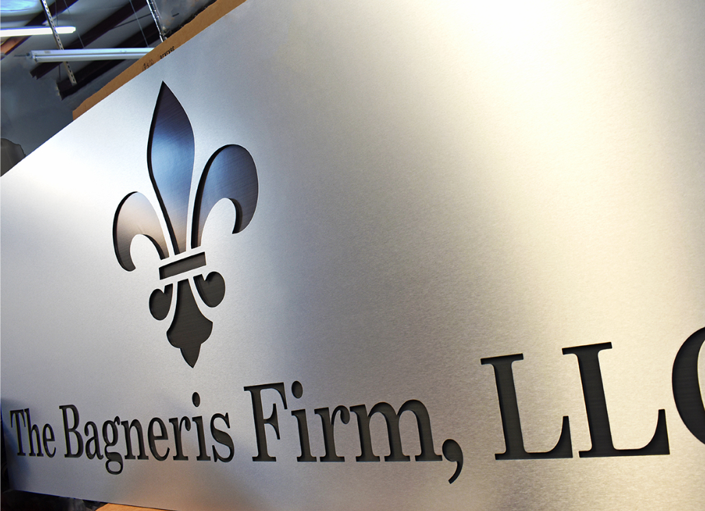 Brushed silver aluminum business sign with fleur de lis graphic and text that reads: The Bagneris Firm, LLC