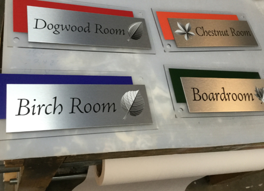 Four brushed silver Engraved Metal door signs with text that reads: Dogwood Room, Chestnut Room, Birch Room, Boardroom