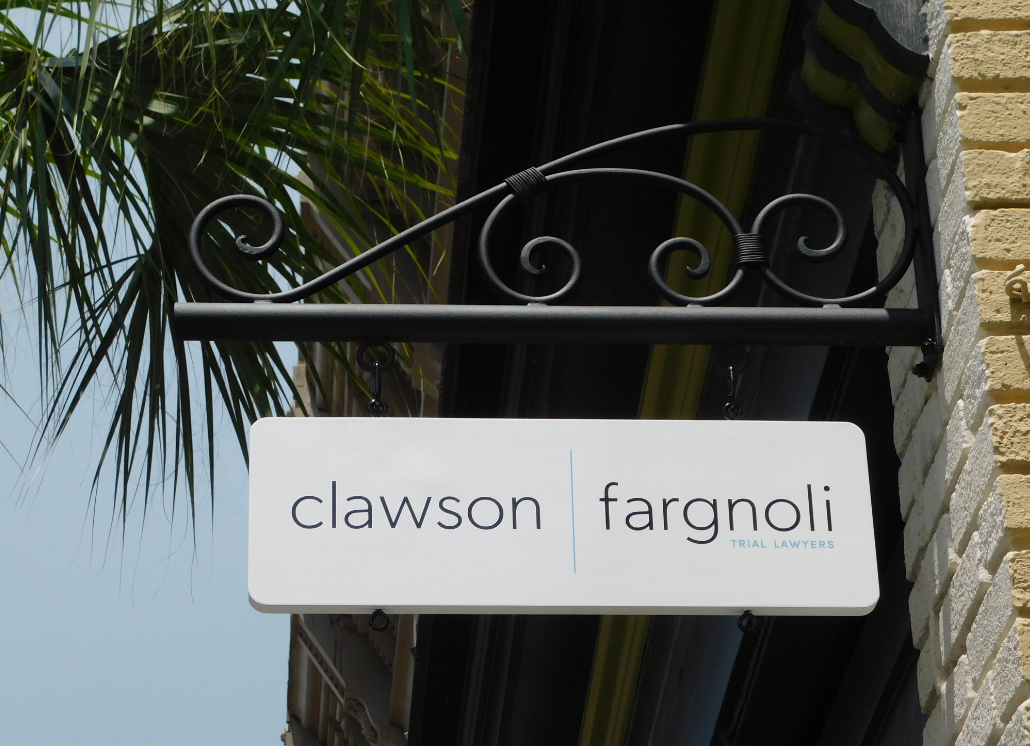 Blue, black, and white projection sign with text that reads: clawson | fargnoli Trial Lawyers