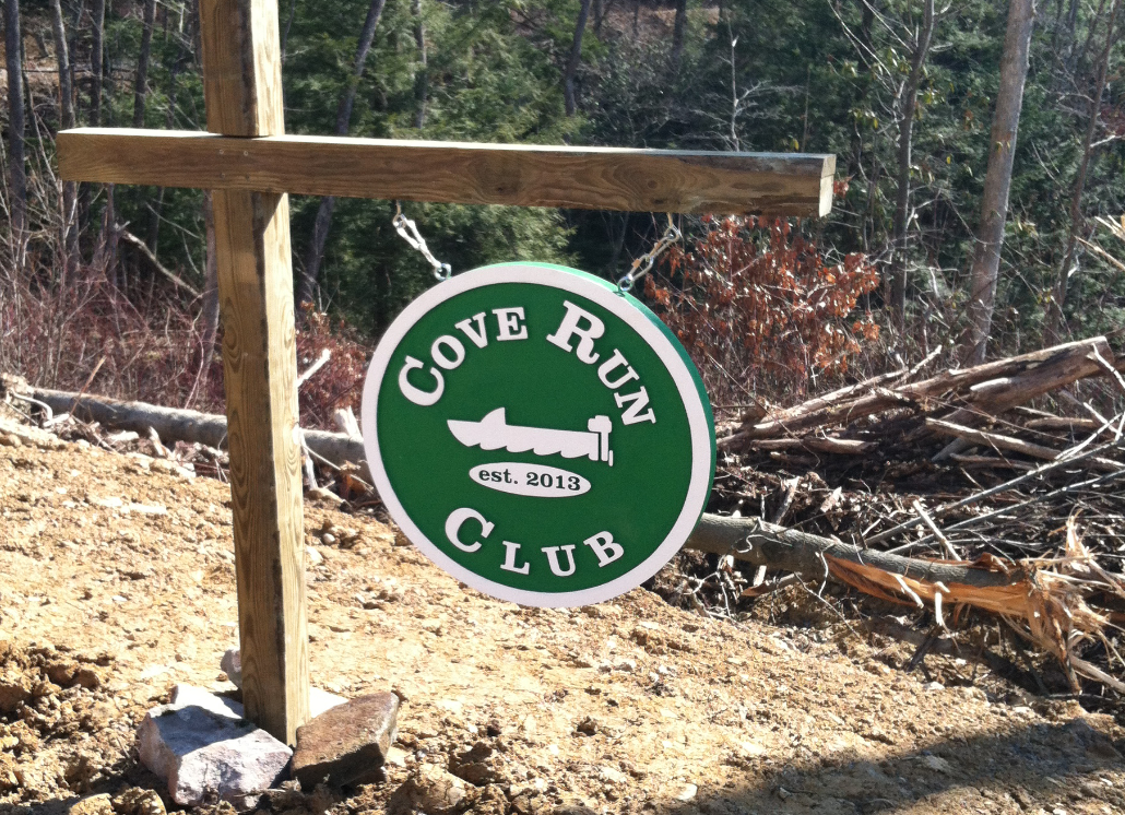HDU outdoor hanging sign with a boat graphic, wilderness in the background, and text that reads: COVE RUN CLUB