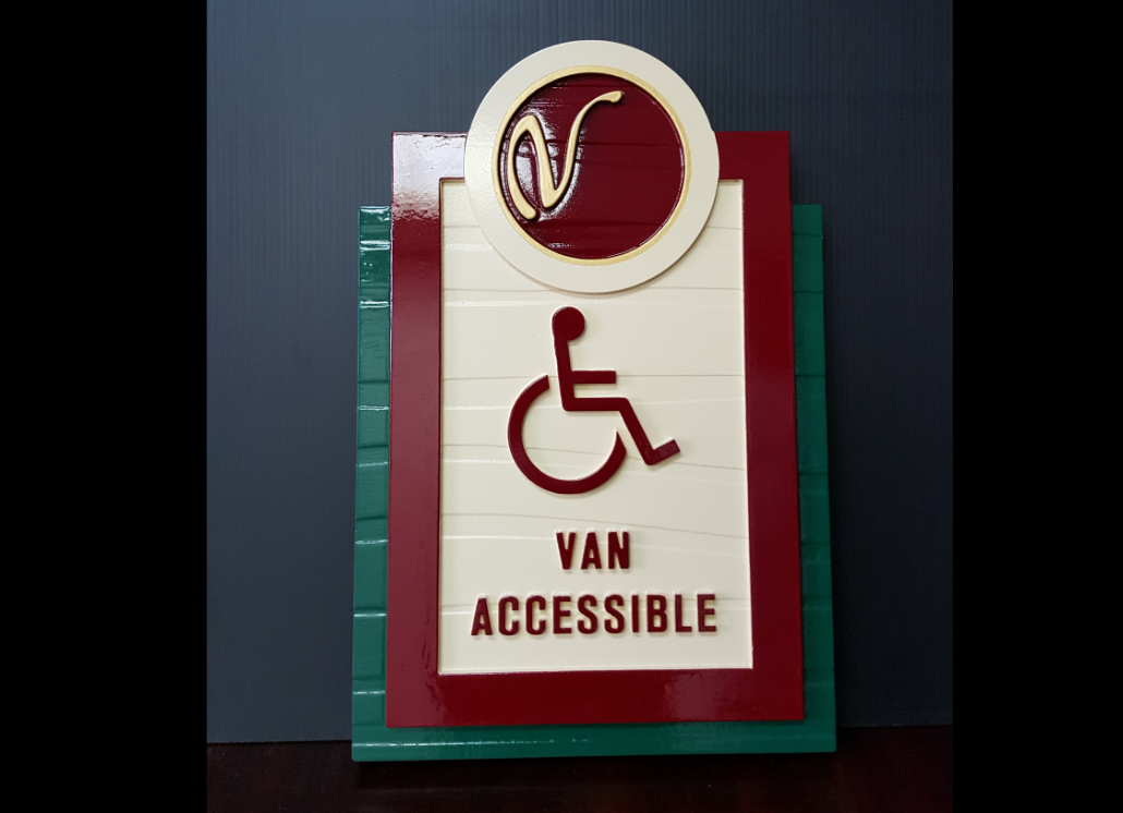 Green, burgundy, and white HDU ADA sign with graphic of wheel chair and text that reads: VAN ACCESSIBLE
