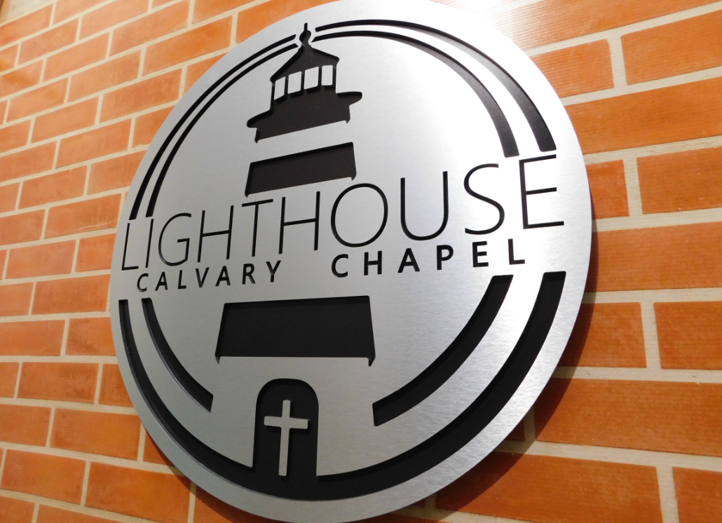 Oval-shaped brushed silver dibond sign with lighthouse graphic and text that reads: LIGHTHOUSE CALVARY CHAPEL.