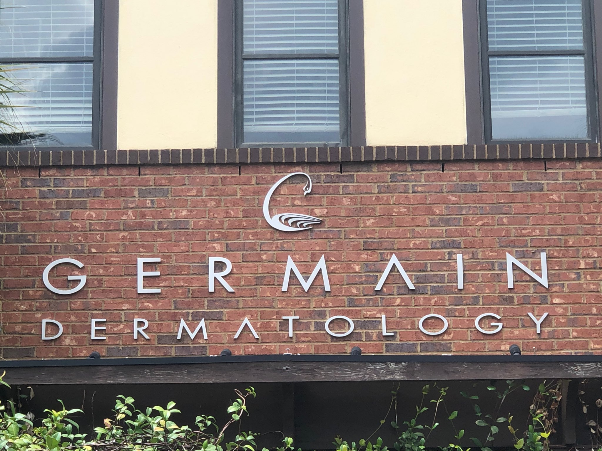Brushed silver metal letters on a brick wall outdoors with text that reads: GERMAIN DERMATOLOGY