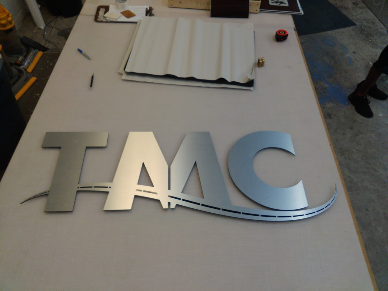 Brushed silver metal letters with text that reads: TMC