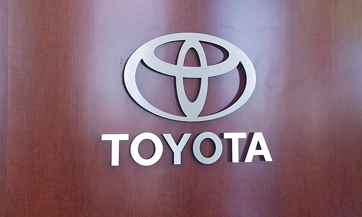 Metal 3D lettering indoors on wooden background with Toyota logo and text that reads: TOYOTA