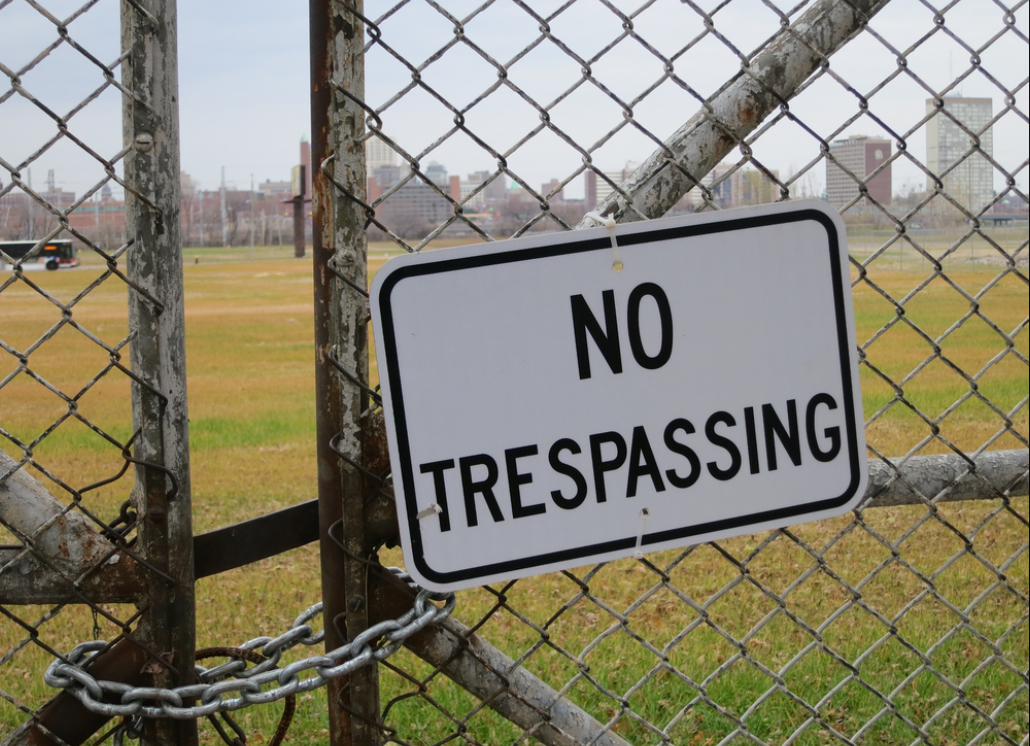 Aluminum No Trespassing Reflective Sign Mounted on Metal Fence