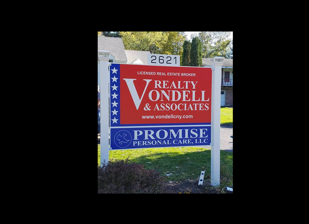 Wooden Sign for Realty Company Mounted between Two Post